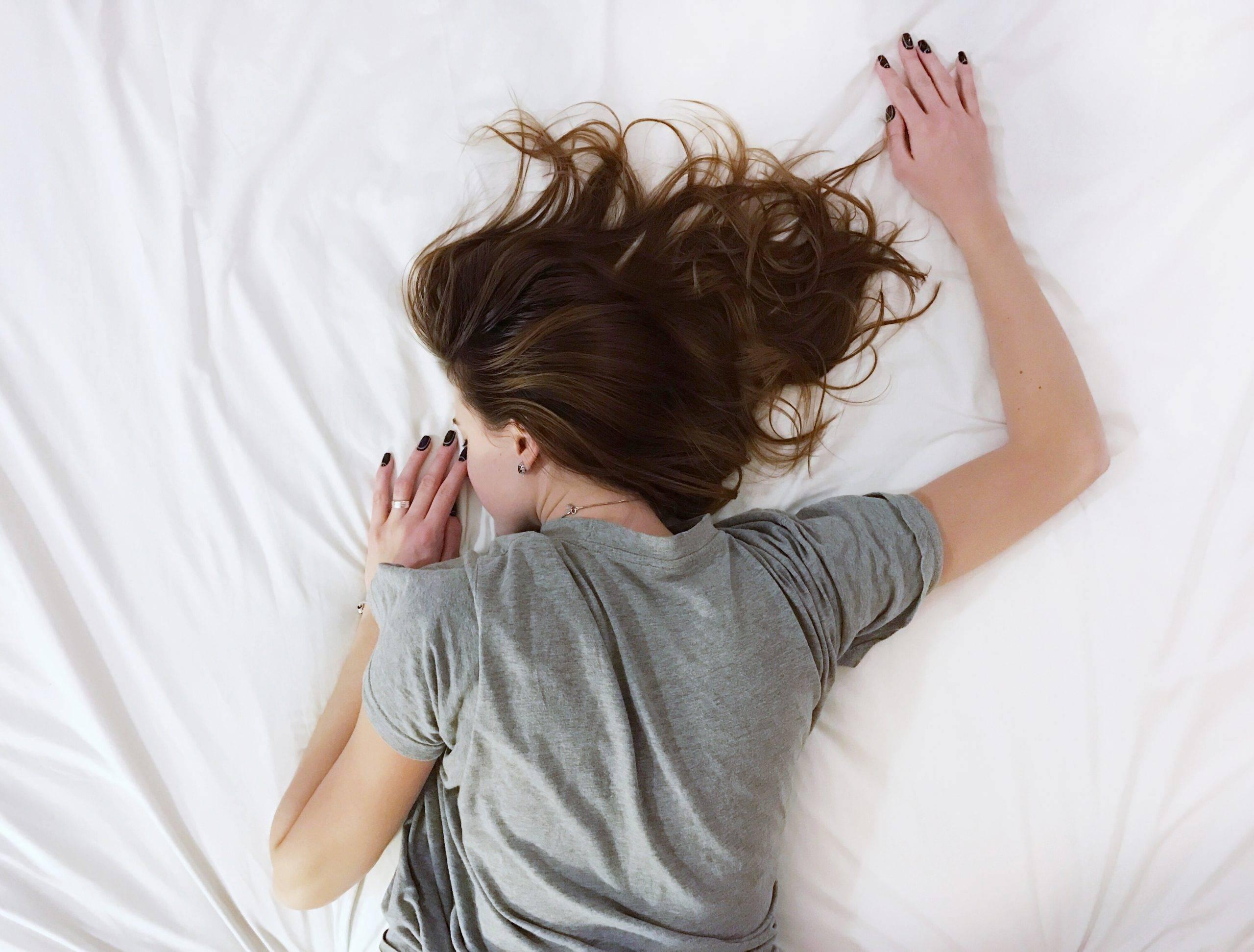 Jak rozpoznać depresję i jak sobie z nią poradzić wg medycyny chińskiej? Załamana dziewczyna w szarym t-shircie leży na brzuchu na łóżku na białym prześcieradle.