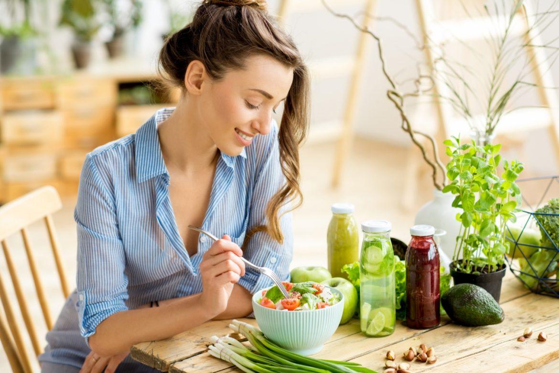 Alicja Kalińska opowiada o tym, jak wypracować dietę na całe życie. Kobieta w niebieskiej koszuli siedzi przy stole i je zdrową sałatkę.