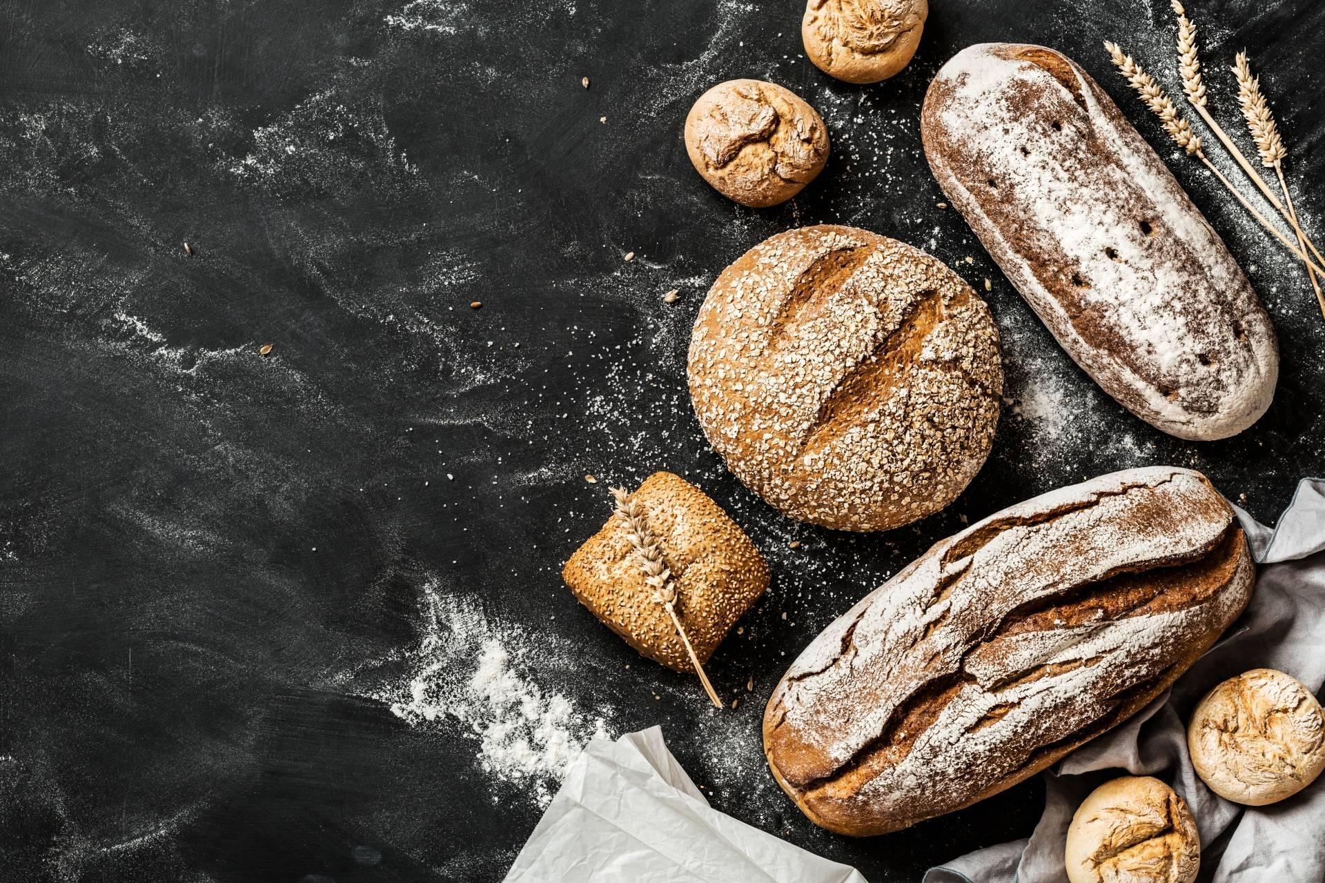 Dieta przeciwgrzybicza - wyeliminuj gluten. Bohenki świeżego chleba oprószone mąką na ciemnym tle.