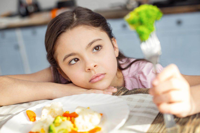 Autyzm i dieta, dieta w autyzmie - czy sposób żywienia może zwiększyć komfort życiowy dziecka opowiada dietetyczka kliniczna dr. n. med. Justyna Jessa (Mama dietetyk). Na zdjęciu autystyczna dziewczynka siedzi przy stole nad talerzem warzyw i przygląda się z oddali brokułowi nadzianemu na widelec.