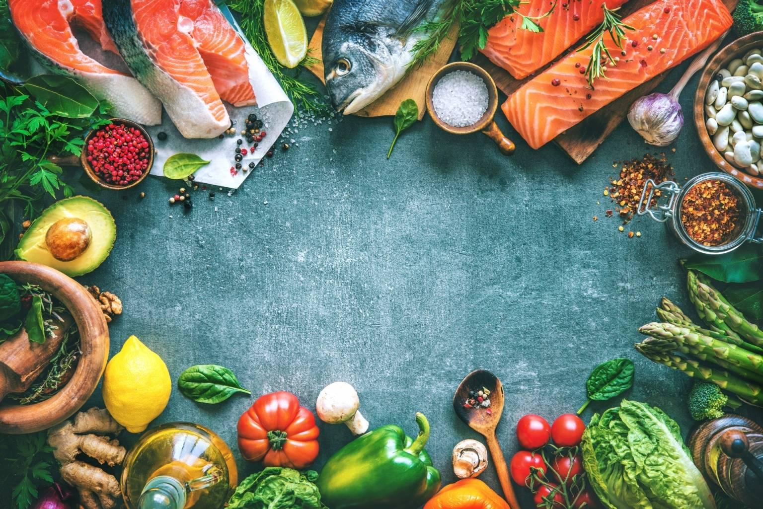 Cukrzyca typu 2 - jak ją leczyć? Na szarym tle poukładane są w kółku produkty żywnościowe: ryby, warzywa, owoce, nasiona i przyprawy.
