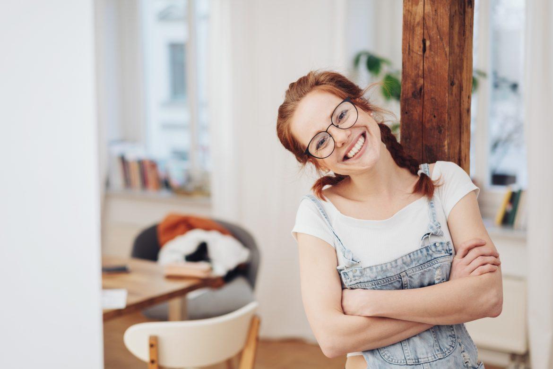 Gelotologia - śmiech to zdrowie. Czym jest terapia śmiechem? Rudowłosa dziewczyna w białej bluzce i jeansowych ogrodniczkach opiera się o drewnianą belkę w swoim domu.