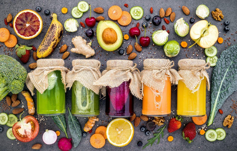 Przepisy na koktajle na odporność. Widok z góry na słoiki z kolorowymi, domowymi koktajlami i smoothies warzywno-owocowymi.