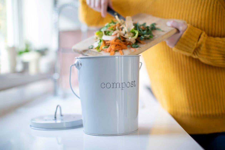 Jak zrobić kompostownik? Wszystko o domowym kompoście. Kobieta wrzuca resztki organiczne do pojemnika na bioodpady.