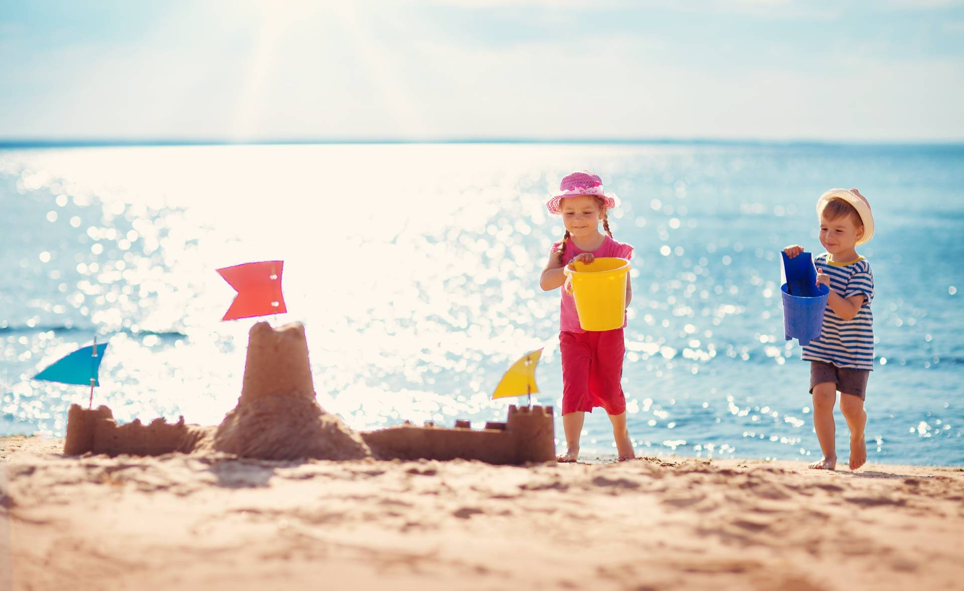 Dzieci budują zamek z piasku na plaży. Jak chronić dziecko przed upałem i udarem słonecznym?