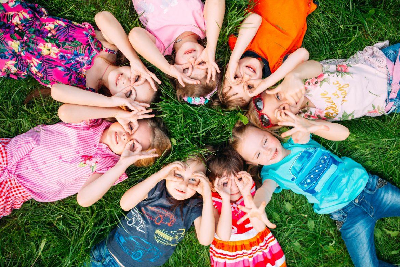 Mononukleoza zakaźna - jakie są jej objawy, przyczyny i jak ją leczyć. Grupa dzieci leżących na trawie w kółeczku i przykładających dłonie do oczu na kształt lornetki.