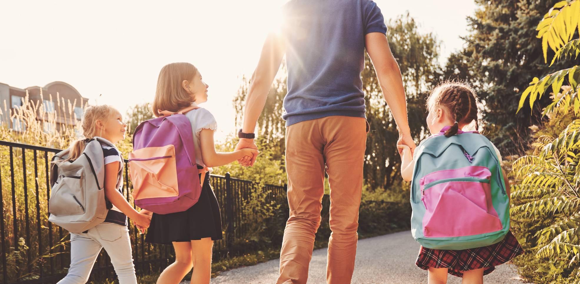 Jak bezpiecznie nosić szkolny plecak? Tata odprowadza dzieci do szkoły.