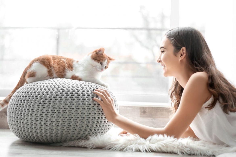 Felinoterapia - na czym polega terapia w towarzystwie kota? Młoda dziewczyna bawi się z kotem w domu.