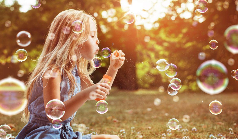 Astma u dzieci - jak rozpoznać objawy i jak leczyć? Blondwłosa dziewczynka puszcza bańki mydlane w letniej sielankowej scenerii.