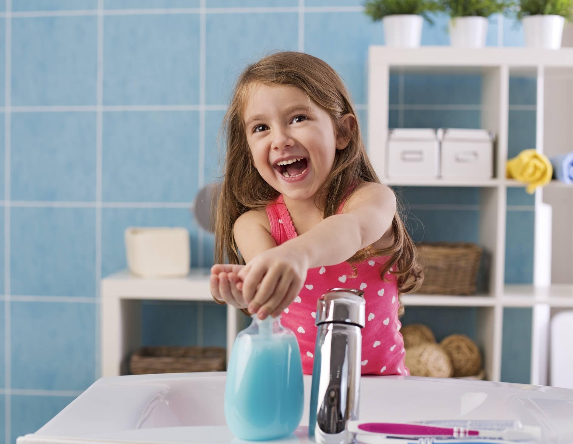 Pasożyty u dzieci - jakie są objawy i jaj je leczyć? Uśmiechnięta dziewczynka myje ręce.