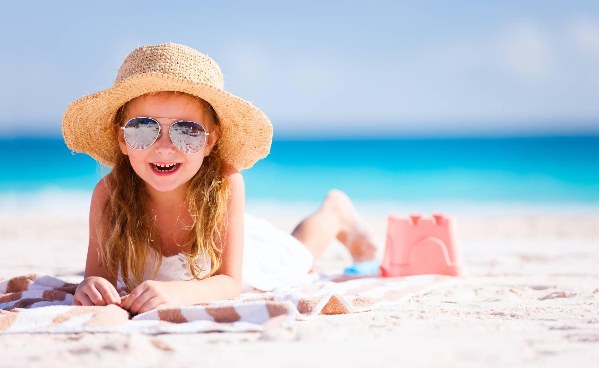 Dziewczynka w okularach przeciwsłonecznych i kapeluszu słomkowym opala się na plaży. Jak chronić dziecko przed udarem słonecznym?