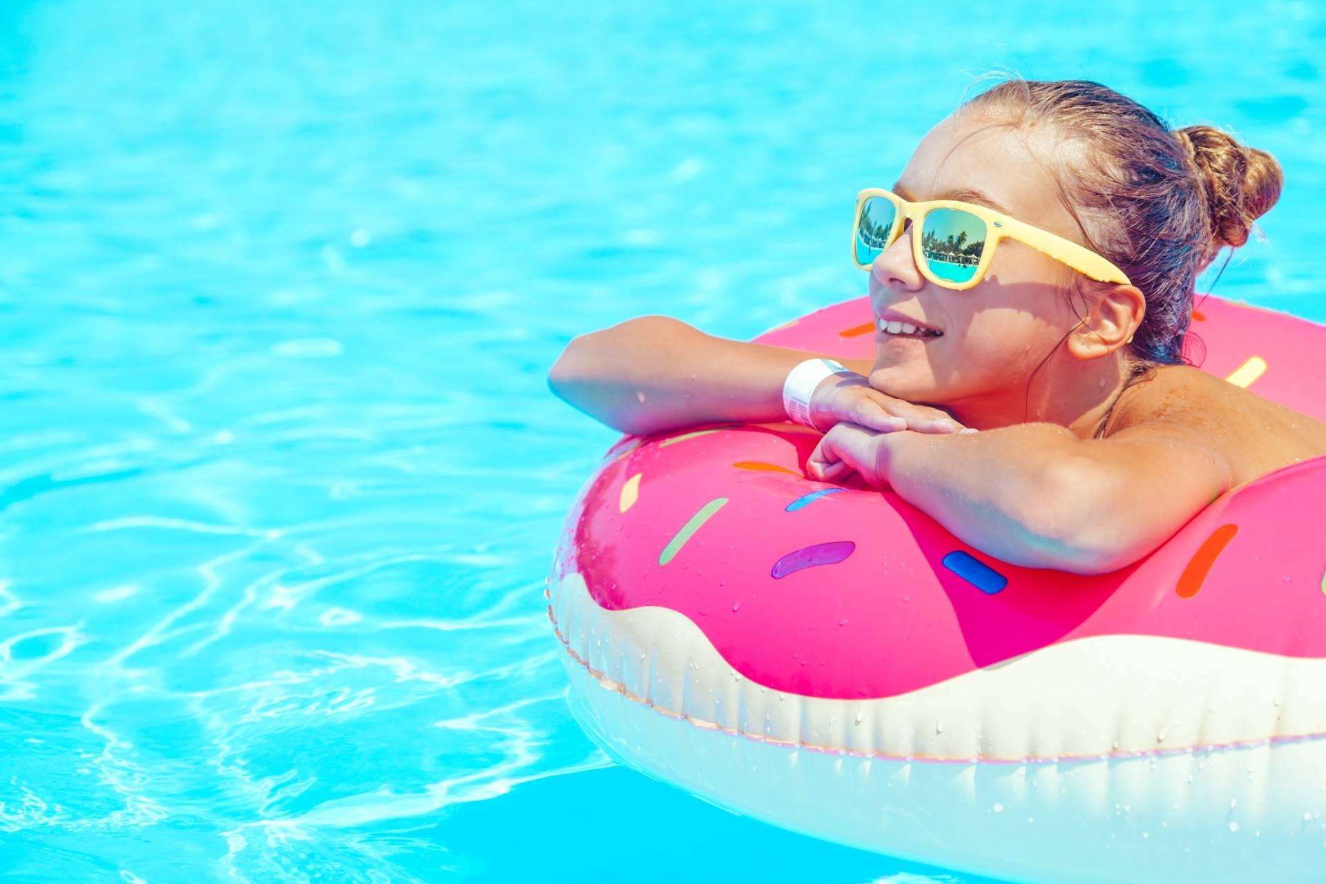 Mała dziewczynka w okularach przeciwsłonecznych pływa w basenie na pontonie.