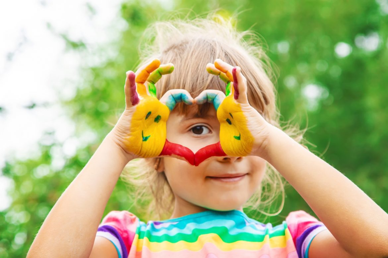 Dr n. med. Paweł Grzesiowski przestrzega przed trzymaniem dzieci pod sterylnym kloszem - dajmy się dzieciom ubrudzić. Dziewczynka układa pomalowane kolorową farbą dłonie w kształt serca i przykłada je do oka.