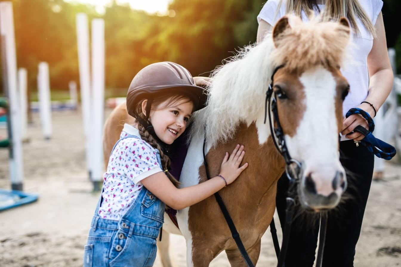 Relacje dzieci ze zwierzętami. Mała dziewczynka w toczku na głowie przytula się do kucyka na wybiegu w stajni.