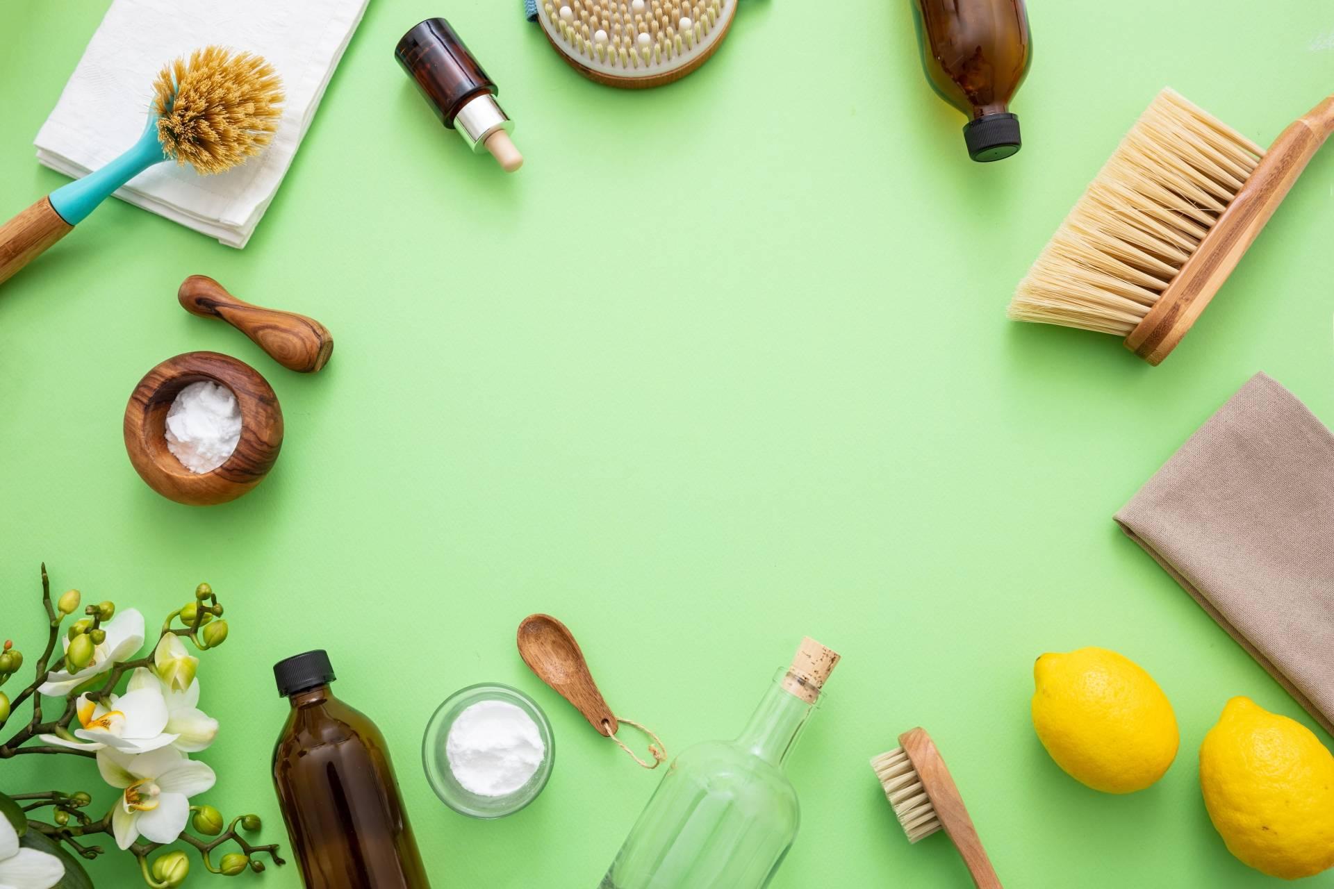 Ekologiczne środki czystości - jak je zrobić samemu? Kompozycja szczotek i środków czystości na zielonym tle.