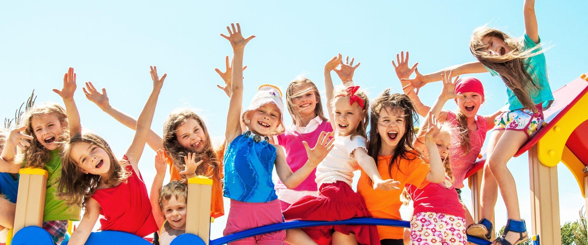 Elektrolity dla dzieci - kiedy je stosować? Grupa kolorowo ubranych szczęśliwych dzieci stoi na mostku.