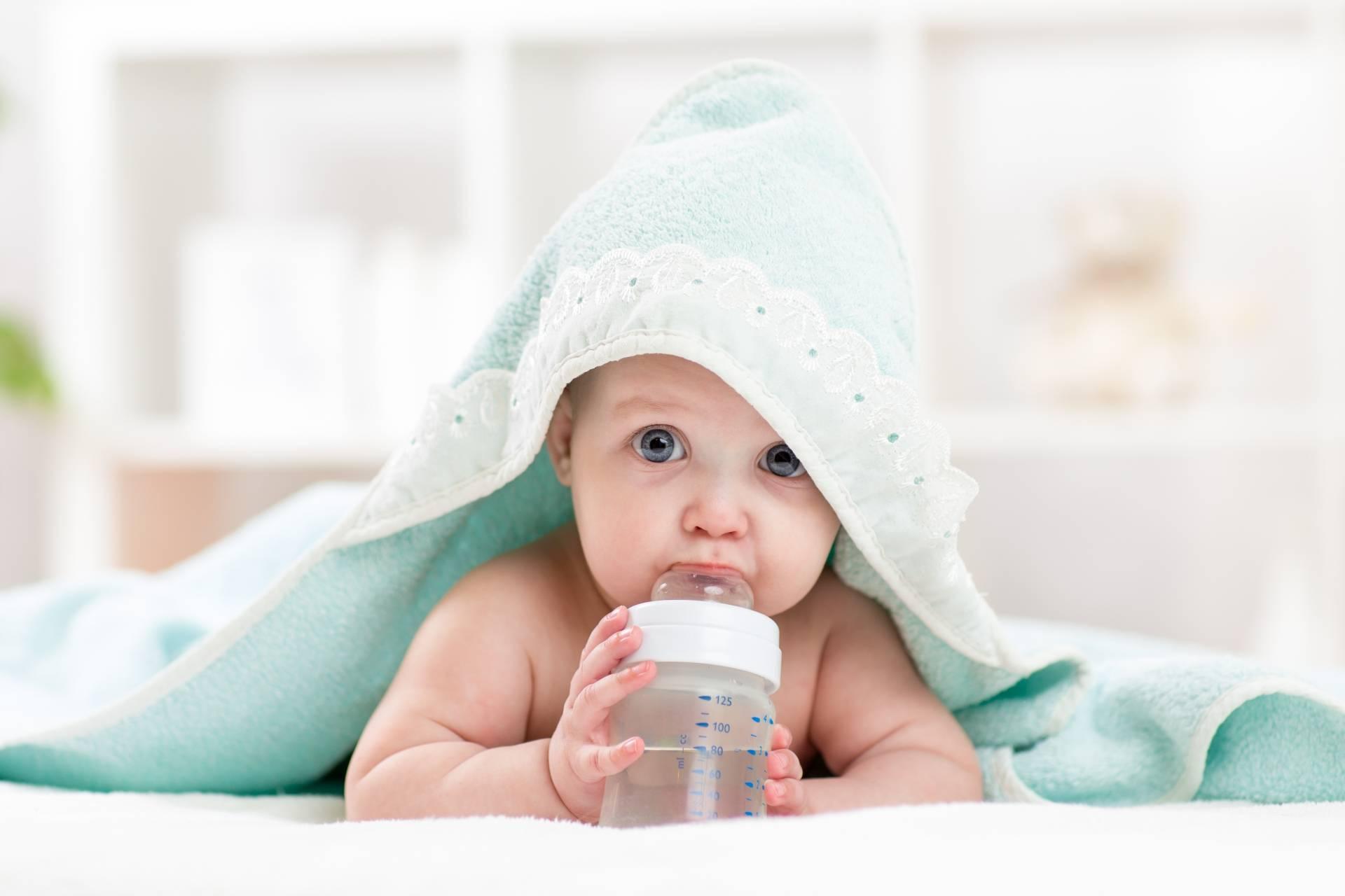 Elektrolity dla niemowląt i dzieci - kiedy je podawać? Niemowlę pod kocykiem pije wodę z butelki.