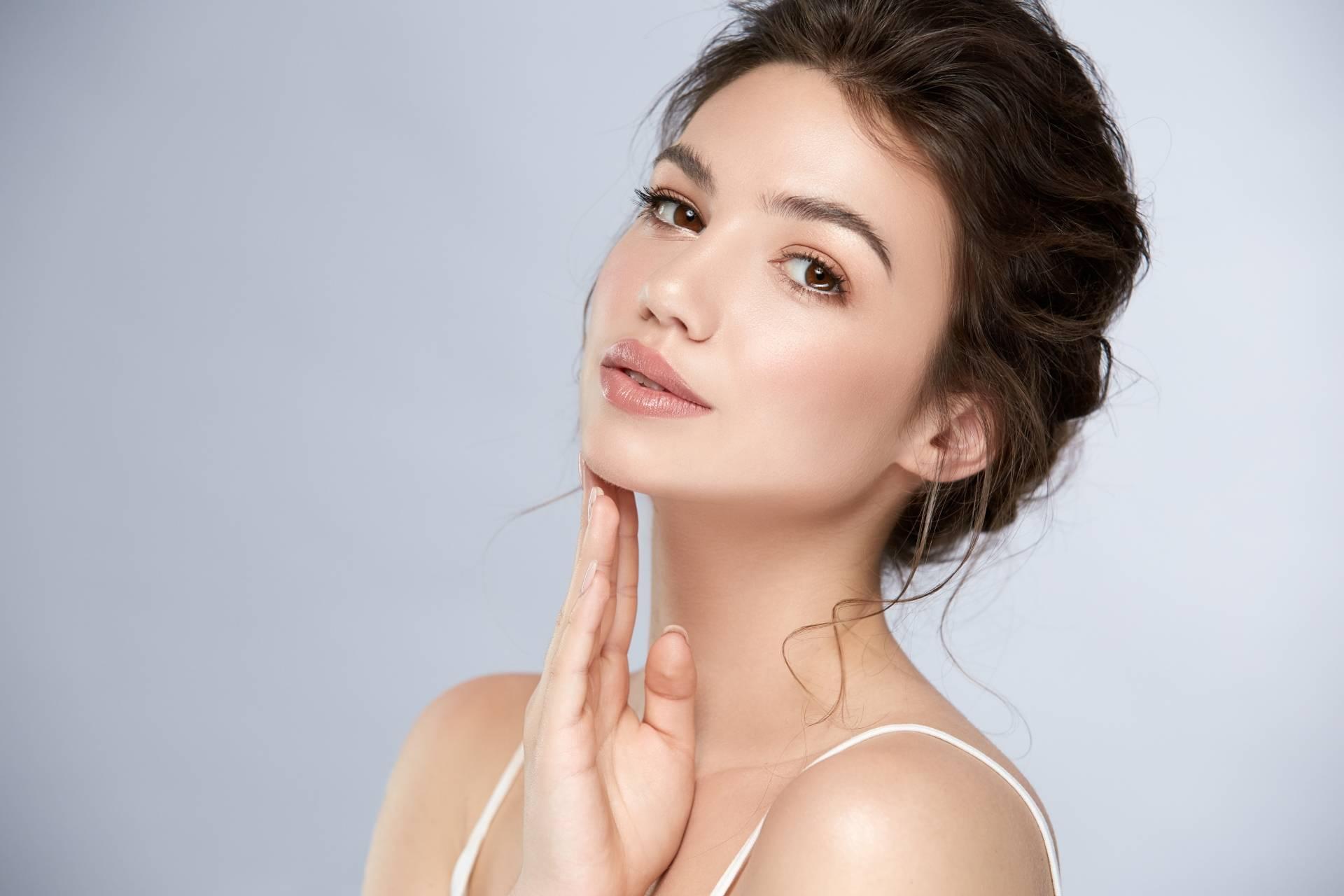 Facemodeling - na czym polega manualna terapia twarzy? Zbliżenie na twarz młodej kobiety, której cera jest świeża i pełna blasku.
