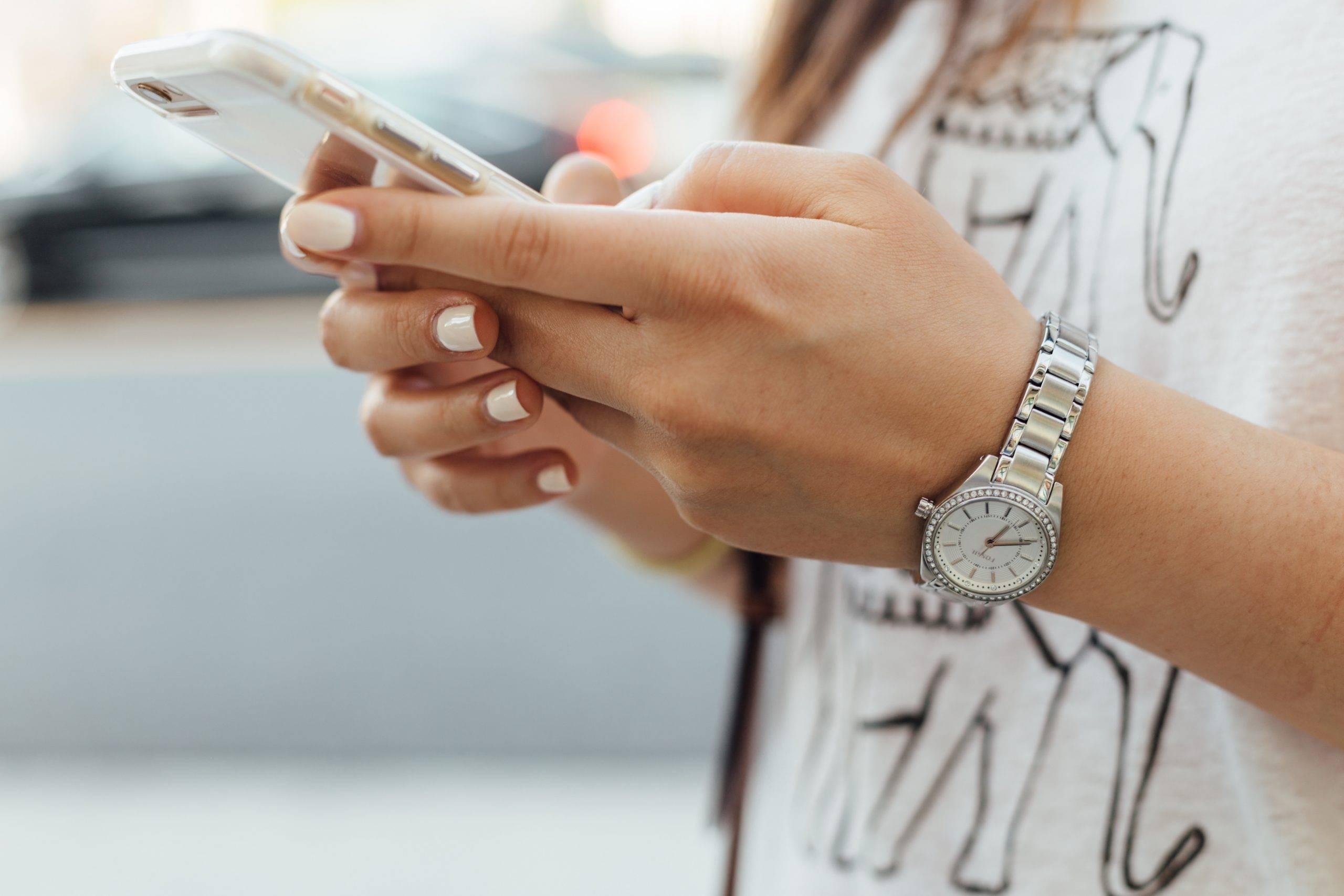Czym grozi FOMO? Dlaczego uzależniamy się od informacji? Kobiece ręce trzymają smartfon.