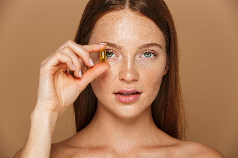 Glutation - czy warto go stosować w formie suplementu diety? Rudowłosa opalona kobieta przystawia kapsułkę do oka.