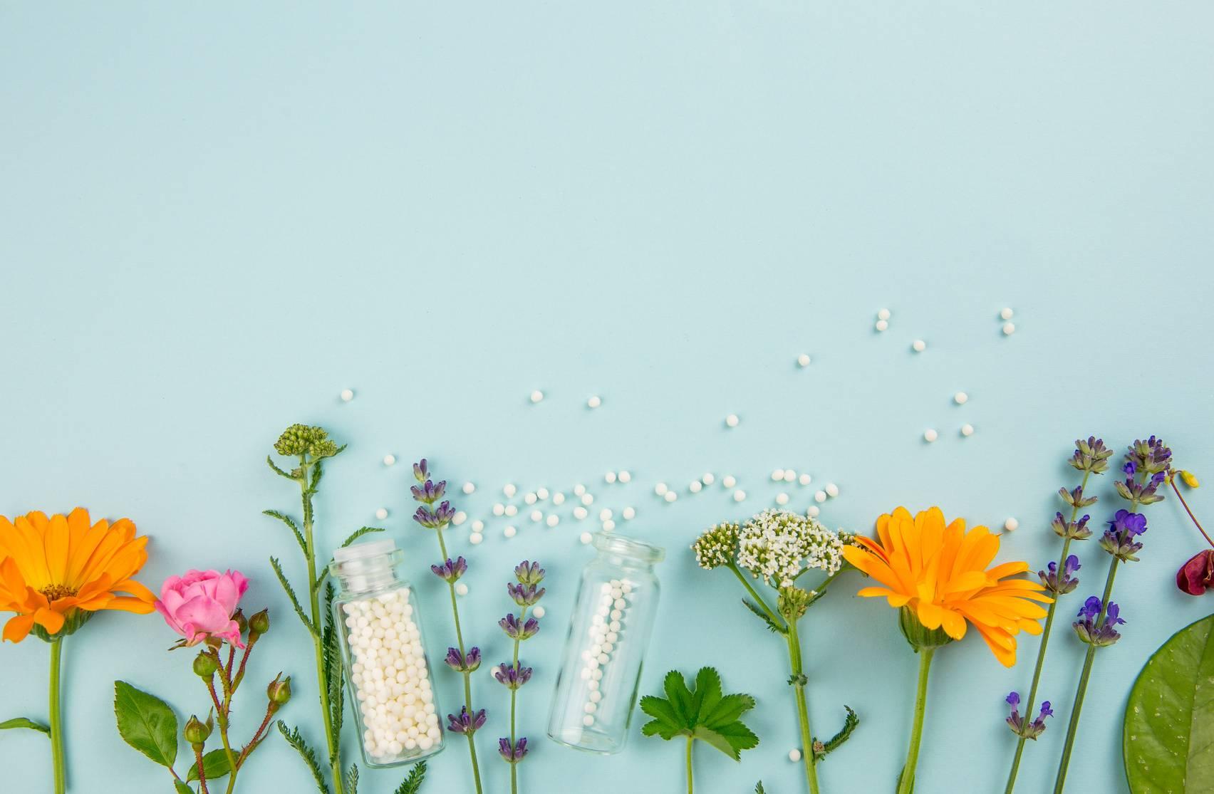 Calcarea carbonica. Leki homeopatyczne, kwiaty i zioła leżą u dołu kadru na niebieskim tle.