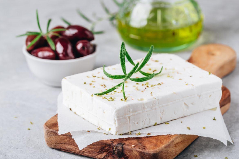 Grecki ser feta na drewnianej desce do krojenia, w tle butelka oliwy i oliwki w miseczce. Przepisy z fetą Agnieszki Żelazko.
