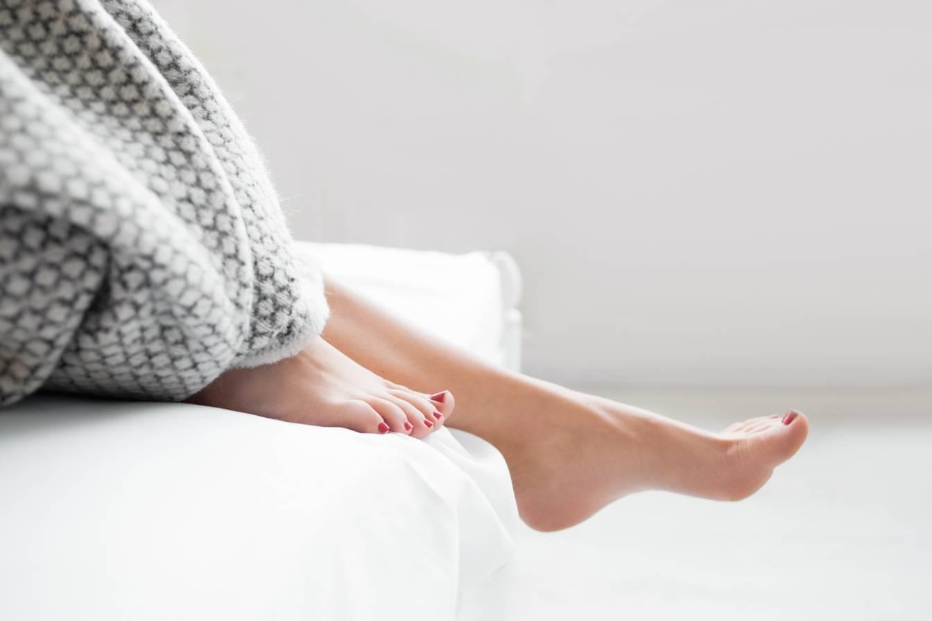 Czym są haluksy? Jak pozbyć się haluksów? Jak uniknąć powstania palucha koślawego. Kobiece stopy z pomalowanymi na czerwono paznokciami wystają spod koca na łóżku w sypialni.