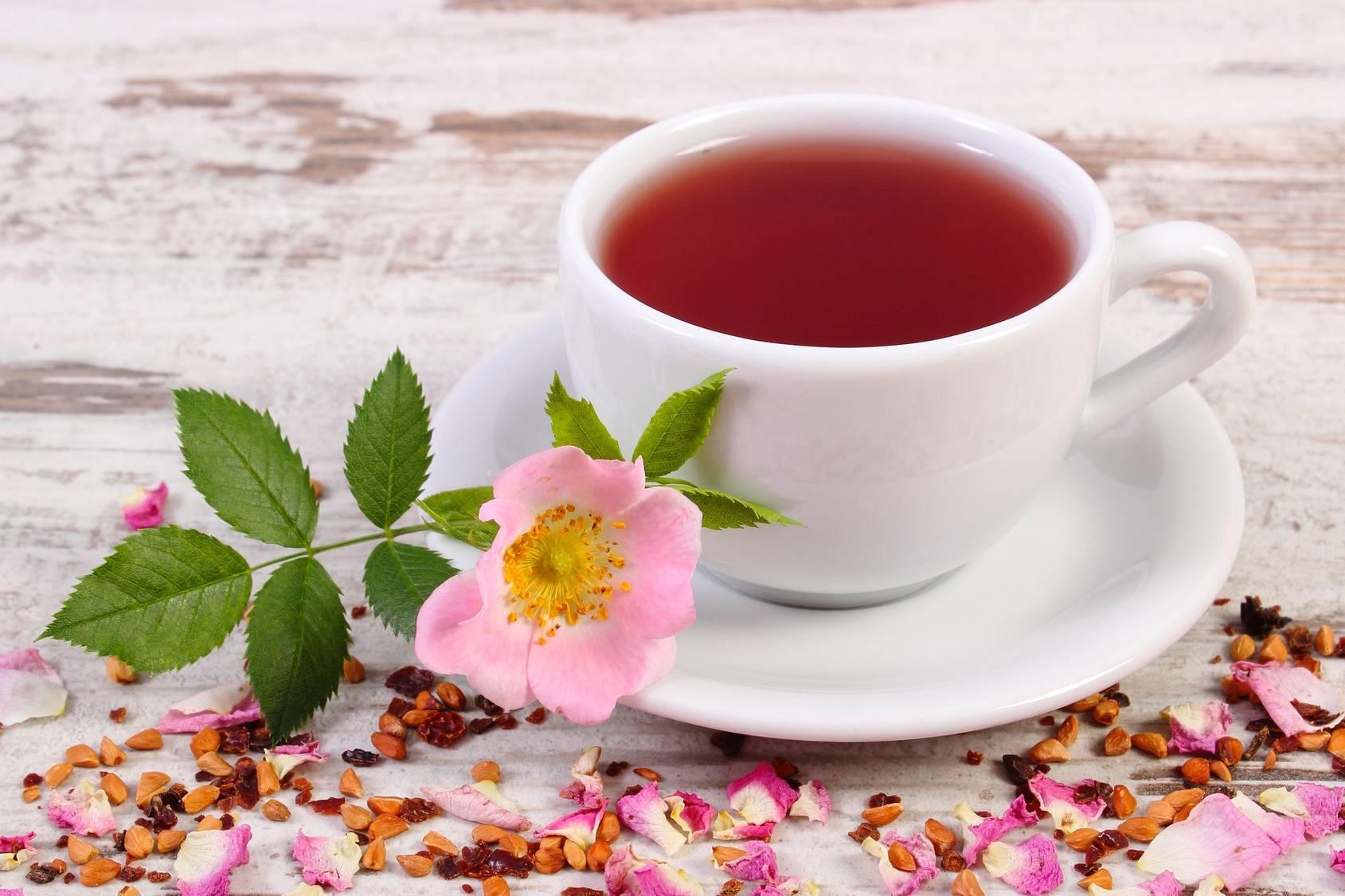 Herbata z dzikiej róży w białej filiżance ze spodkiem stoi na rustykalnym blacie. Obok leżą płatki róży i mała gałązka z kwiatem dzikiej róży.
