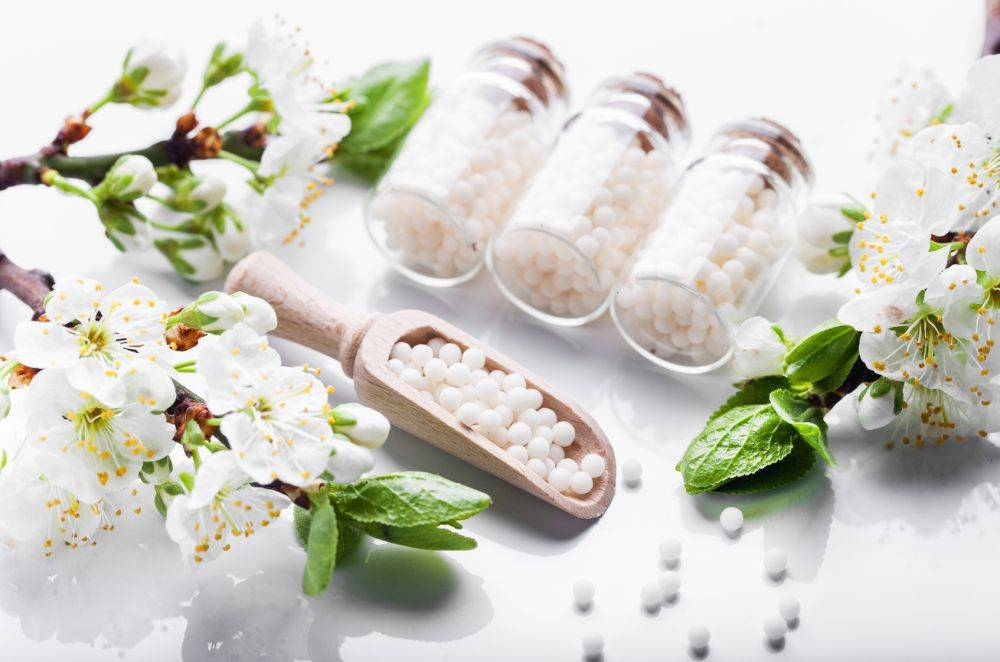 Homeopatia - leki homeopatyczne w słoiczkach ułożone na białym blacie w otoczeniu białych kwiatów jaśminu.
