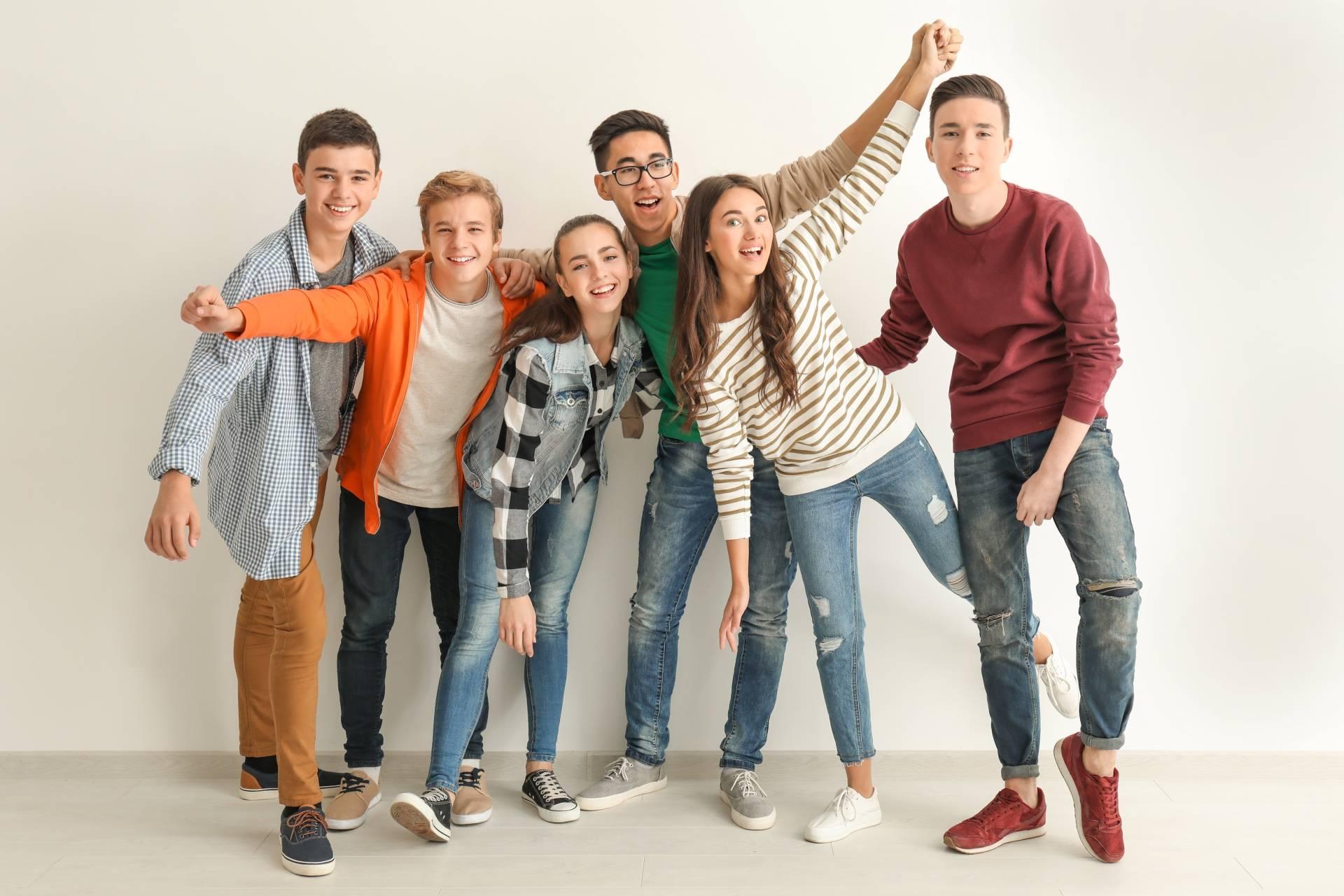 Grupa uśmiechniętych nastolatków pozuje do zdjęcia. Homeopatia dla nastolatków.