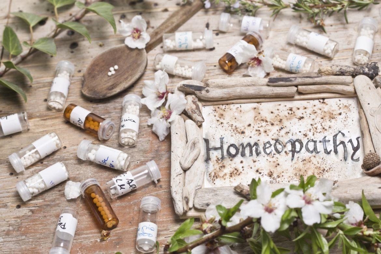 Graphites - lek homeopatyczny. Na drewnianym blacie leżą w nieładzie fiolki leków homeopatycznych i rustykalna tabliczka z napisem homeopatia w języku angielskim.