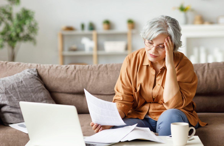 Leki homeopatyczne dla zestresowanych. Starsza zestresowana kobieta czyta ważne dokumenty, siedząc przed laptopem na kanapie w domu.