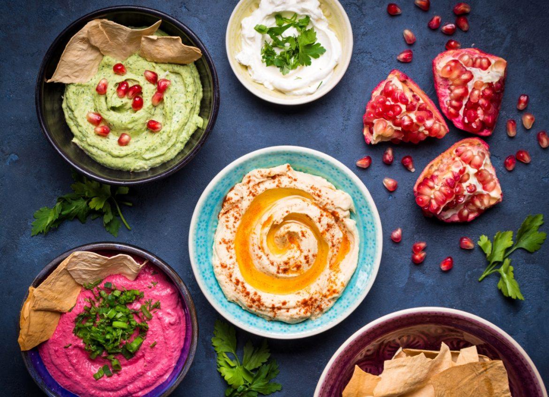 Hummus, ajvar, chimichurri, harissa - 4 przepisy na pasty warzywne na kanapki i nie tylko. Miseczki z kolorowymi pastami warzywnymi na ciemnym blacie.