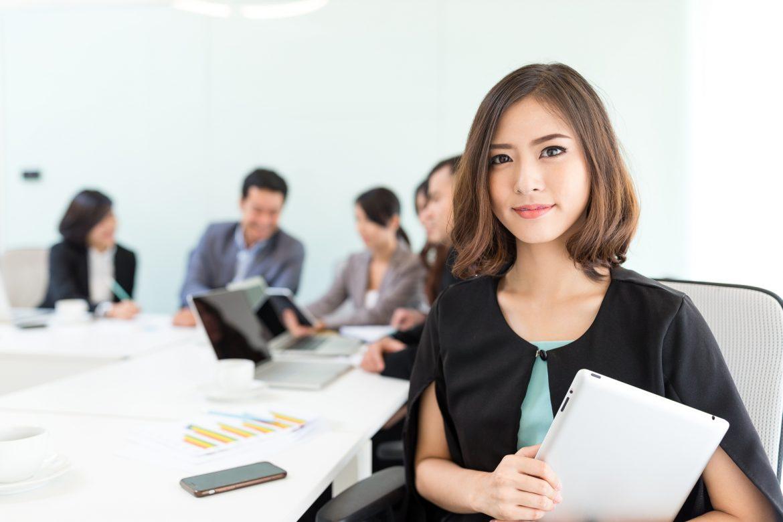 Nunchi - jak odnieść sukces po koreańsku? Piękna Azjatka patrzy w kamerę, a za nią siedzą współpracownicy na spotkaniu biznesowym.