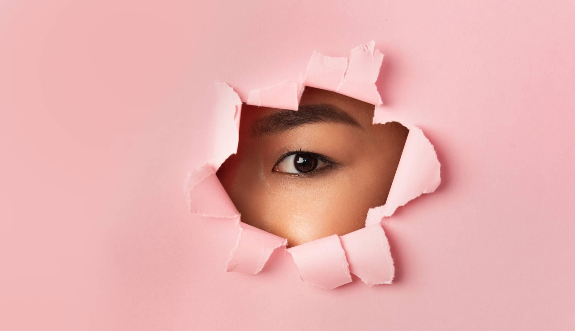 Nunchi - koreański sposób na sukces. Azjatka wygląda jednym okiem przez dziurę w różowej ścianie.