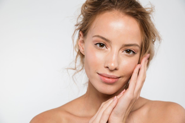 Izotretynoina w leczeniu trądziku - co warto wiedzieć o tej terapii? Młoda kobieta o dobrze nawilżonej i gładkiej twarzy pozuje na białym tle.