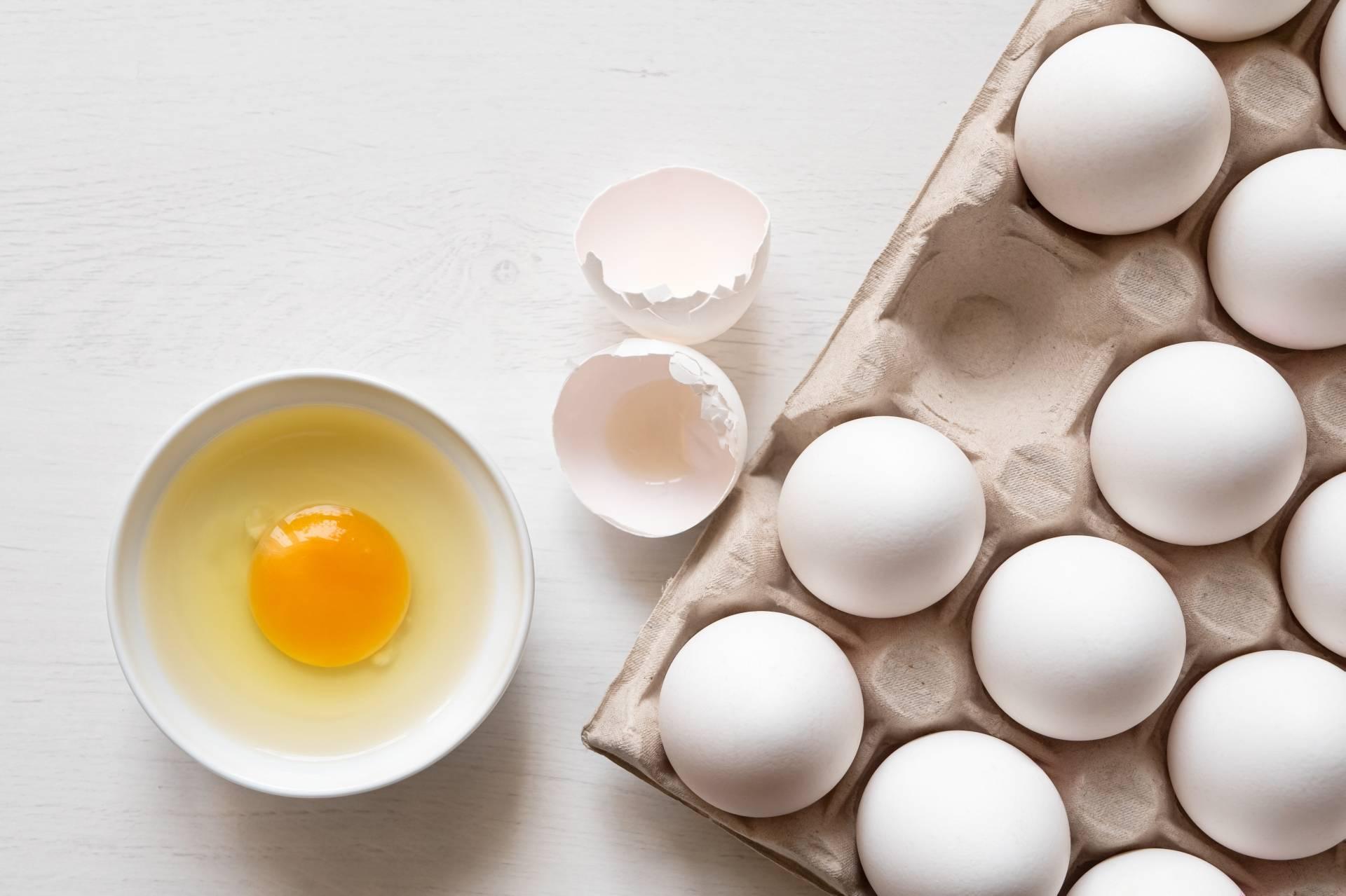 Dieta przeciwgrzybicza. Jajka na białym blacie, obok w miseczce jedno wbite jajko.