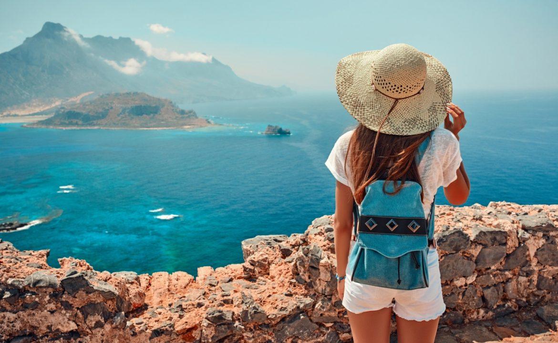 6 zasad jak być eko w podróży - jak zmnieszyć swój ślad węglowy na wakacjach? Dziewczyna w słomkowym kapeluszu i plecaku stoi na skarpie i podziwia panoramę - w tle ocean i skały.