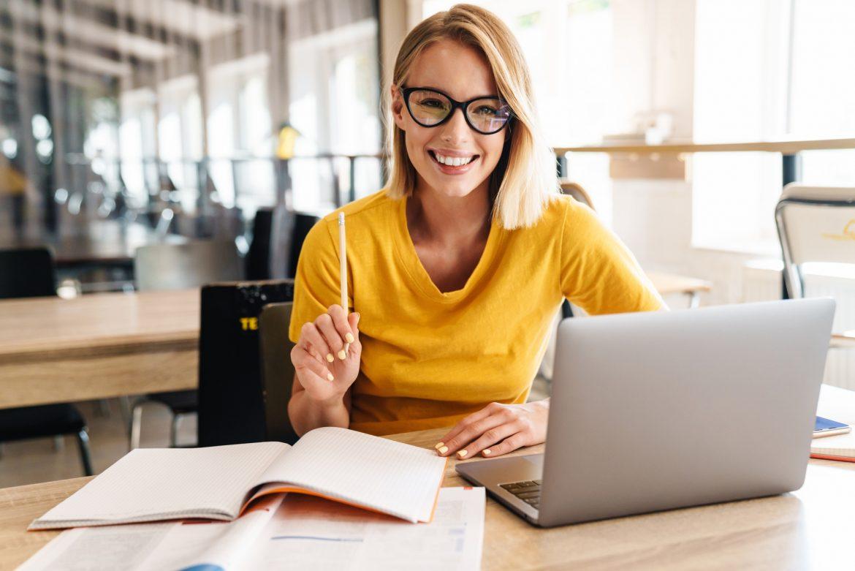 Iloraz inteligencji - czy jesteśmy w stanie zwiększyć swoje IQ? Uśmiechnięta kobieta w okularach i żółtym swetrze siedzi przed laptopem.