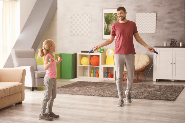 Jak ćwiczyć z dziećmi? Ojciec z córką trenują ze skakanką w domu.