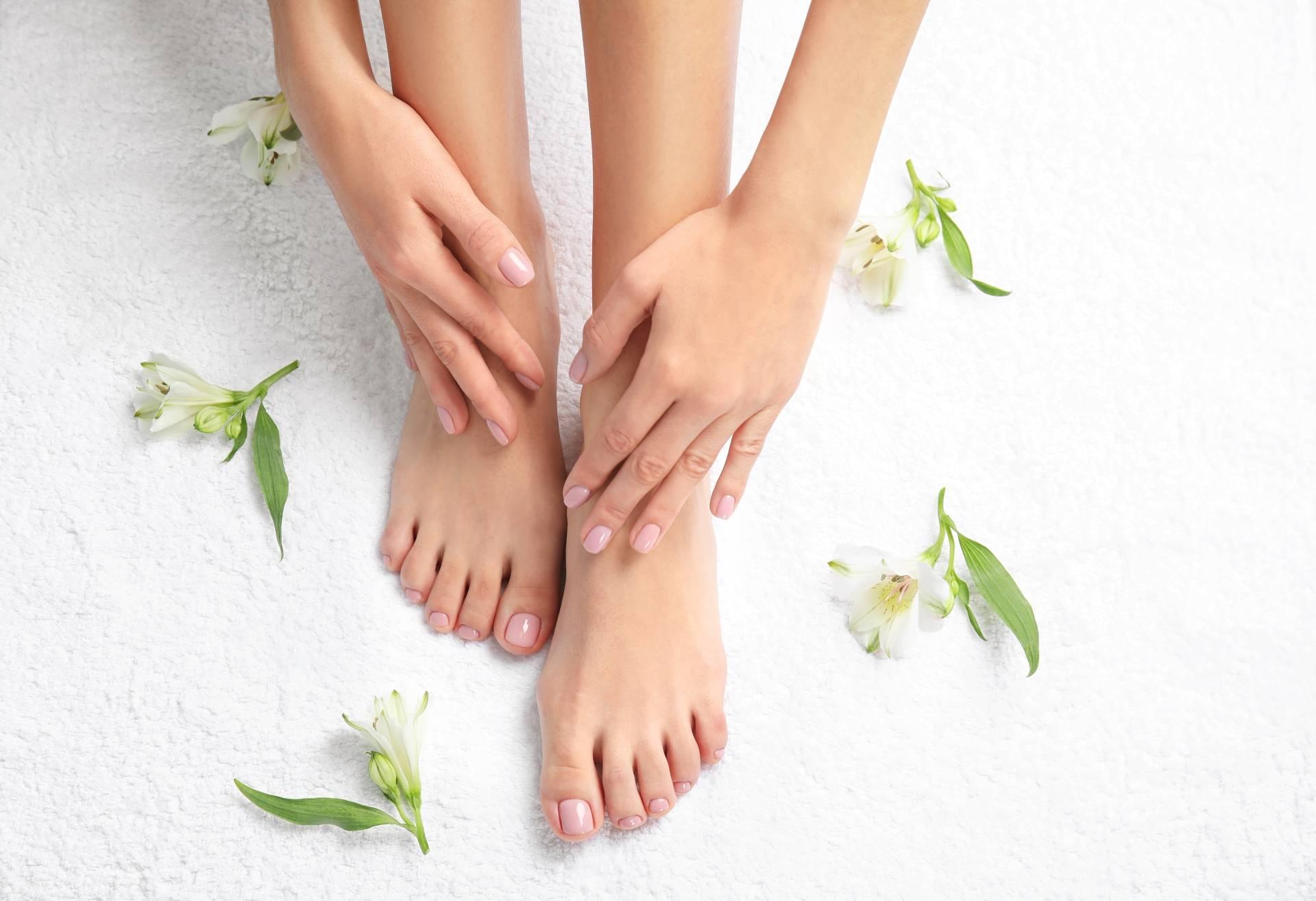 Pękające pięty - jak o zadbać o stopy? Kobieta dotyka rękami swoich wypielęgnowanych stóp. Zbliżenie i widok z góry.