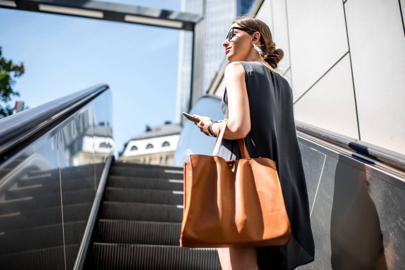 Zarządzanie sobą w czasie - jak zwiększyć efektywność? Młoda kobieta, busunesswoman w czarnej sukience, z brązową skórzaną torbą wjeżdża po schodach ruchomych z podziemi metra na ulicę.