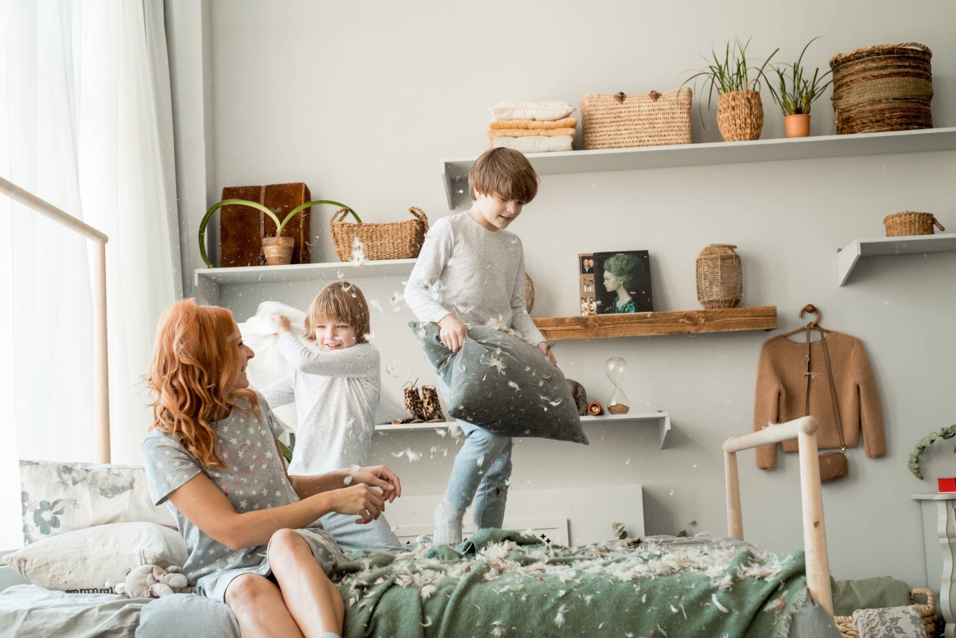 Jak rozwiązywać konflikty między rodzeństwem? Mama siedzi na łóżku i godzi skłóconych braci, którzy walczyli na poduszki.