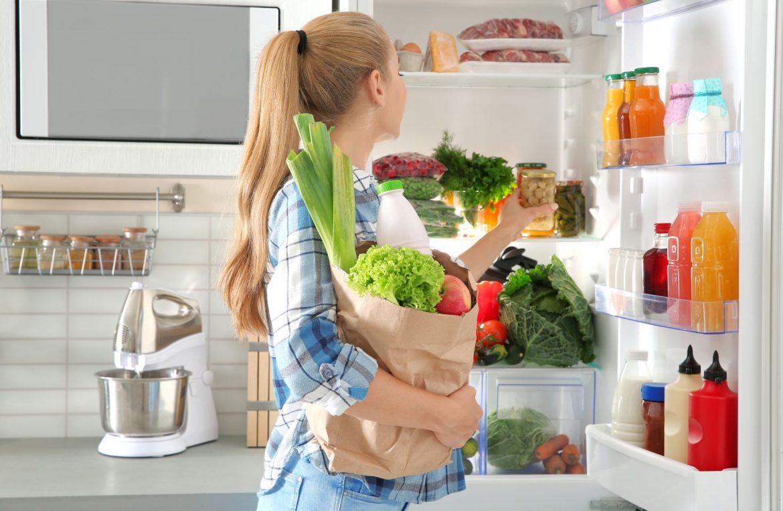 Jak nie marnować jedzenia? Nurt zero waste w kuchni. Kobieta wkłada zakupy do lodówki.