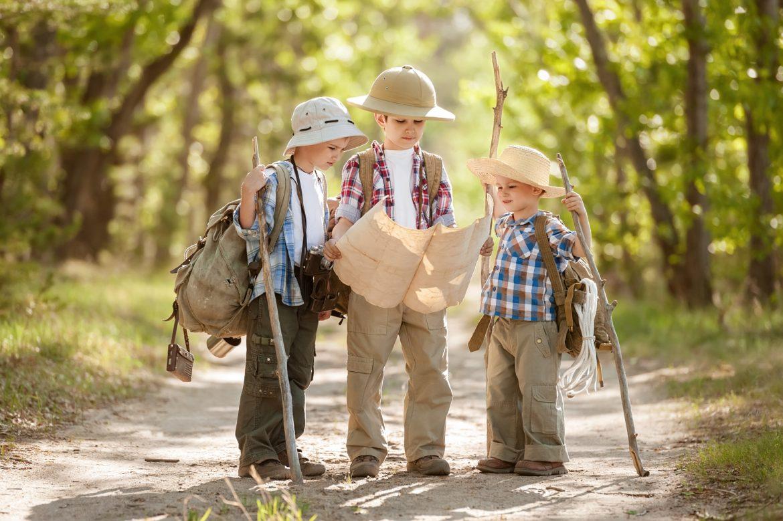 Jak nie zgubić się w lesie opowiada Adam Wajrak. Trzech małych chłopców ubranych jak podróżnicy patrzy na mapę i szuka drogi w lesie.