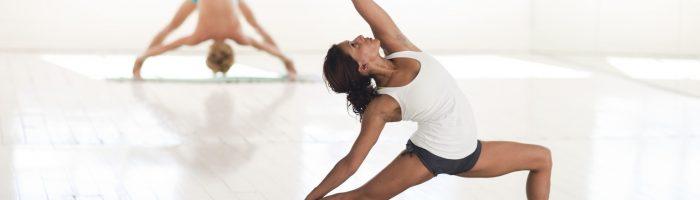 Joga na kręgosłup. Joginka ćwiczy jogę na macie w sali do ćwiczeń. W tle mężczyzna również ćwiczący jogę.