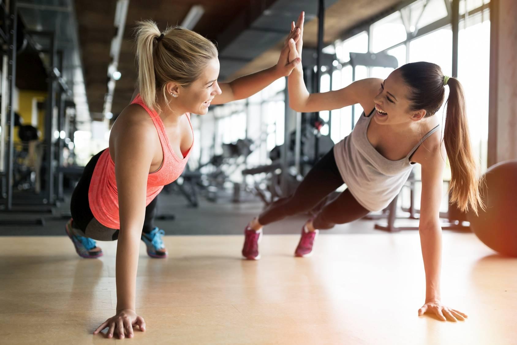 Trening siłowy na siłowni regeneruje organizm i wyszczupla. Dwie koleżanki przybijają sobie piątkę, ćwicząc na siłowni.