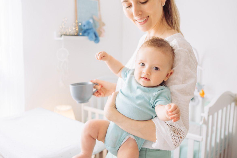 Ból pleców po porodzie - jak zadbać o kręgosłup młodej mamy? Kobieta nosi niemowlę na rękach.