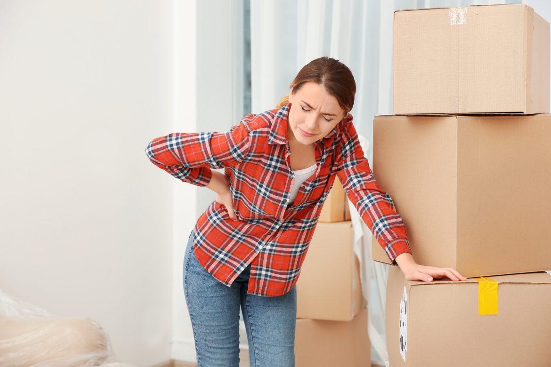 Jak prawidłowo podnosić ciężar? Kobieta trzyma się za kręgosłup lędźwiowy podczas przenoszenia kartonów.