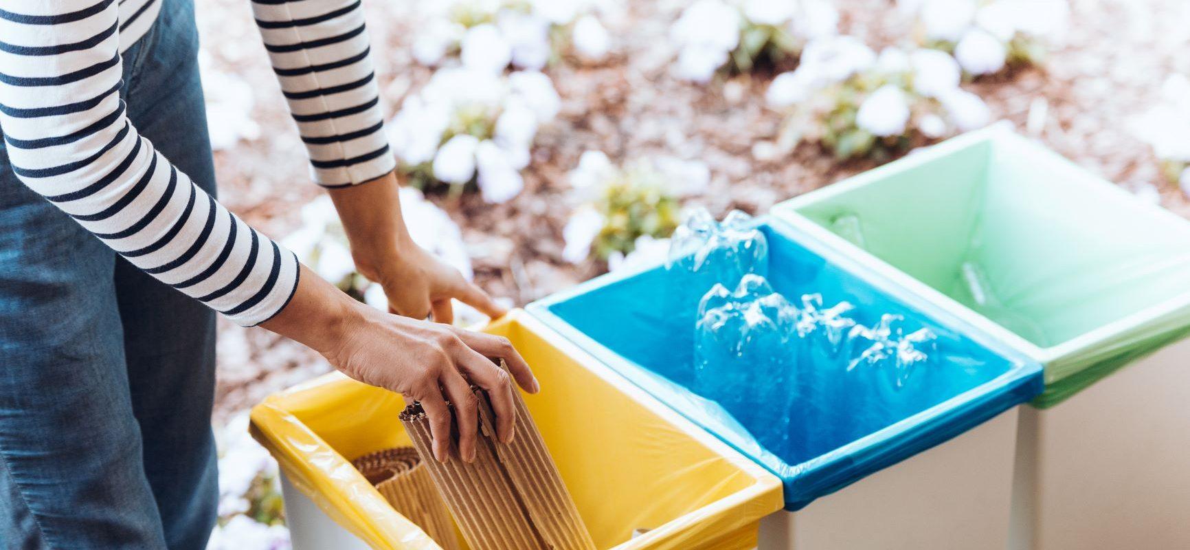 Segregacja śmieci - jak prawidłowo segregować śmieci? Gdzie wrzucać problematyczne odpady typu paragon, lusterko, zatłuszczony papier? Sprawdź naszą ściągawkę! Kobieta segreguje śmieci.
